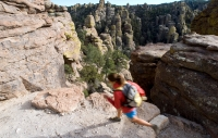 Woman runs along the Echo Canyon Trail (3.3-mile loop) in Chiricahua National Monument. Located in the Northwest corner of the Chiricahua Mountains of Southeast Arizona the monument contains more than 20-miles of trails that wind through towering rock spires, massive stone columns, and enormous rocks balanced on small pedestals. Erosion carved along weak vertical and horizontal crack forming the fascinating rock forms.